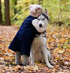 Little girl hugging a husky.